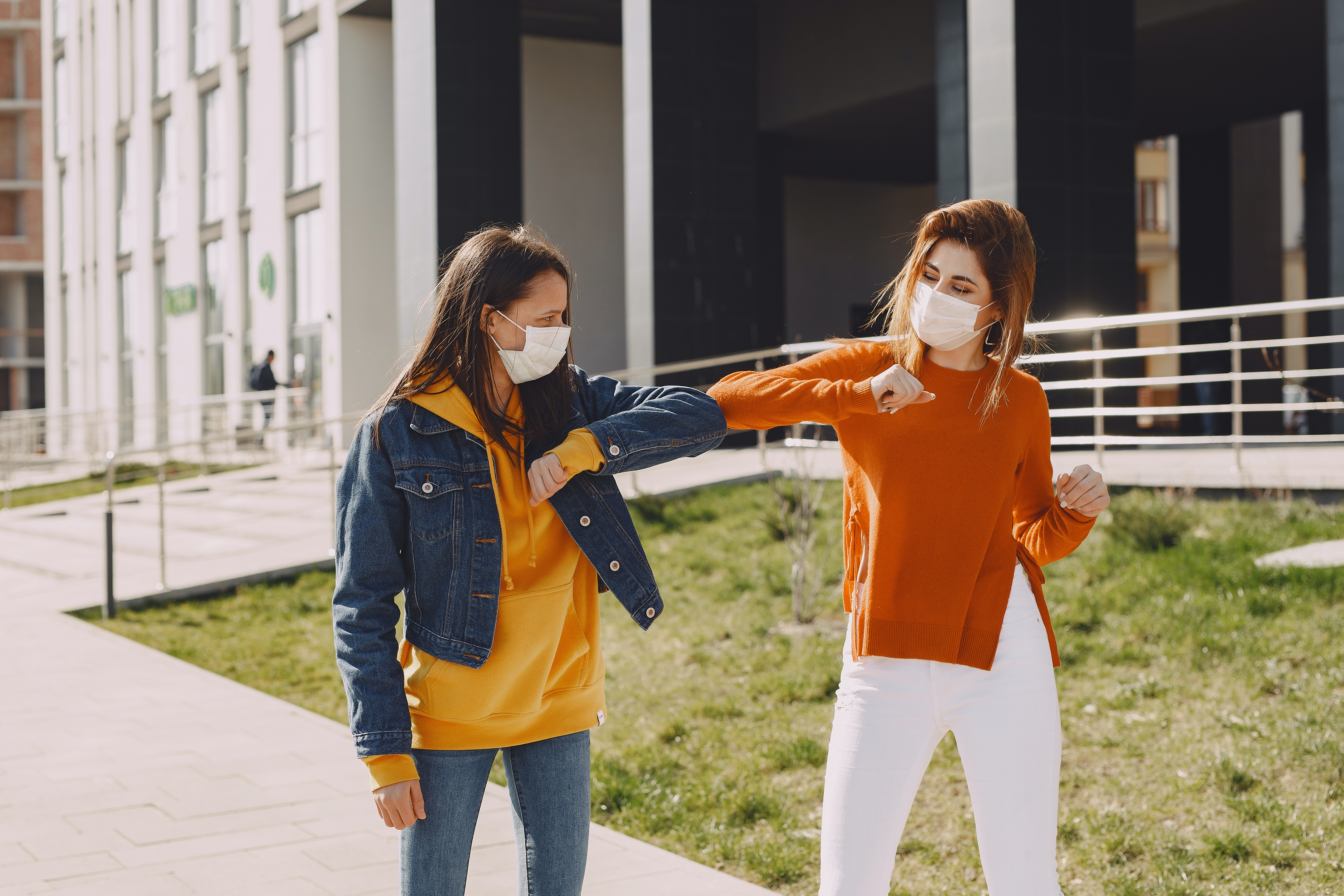 Masked women elbow bump while visiting each other outside