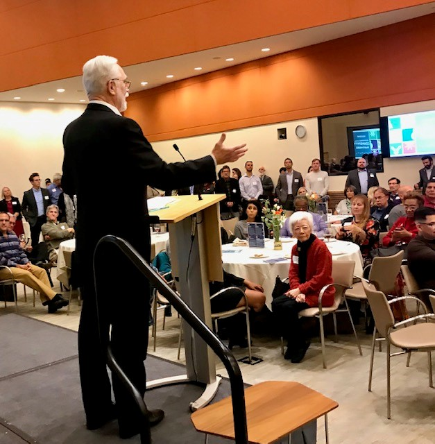 CEO Paul Vandeventer speaks at the podium on stage at the California Endowment's Yosemite Room, addressing approx. 200 holiday party attendees