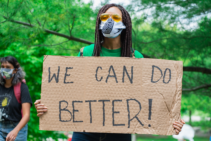 "A Black woman holds a sign at a Black Lives Matter protest that says, ""We Can Do Better!"""